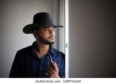 An young tall, dark and handsome Indian Bengali man in a blue shirt, cowboy hat and a pipe in hand  standing in front of a window in studio background. Indian lifestyle and fashion.
