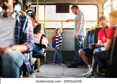 Young tall father and his little son are standing at the rear end of the bus and looking at each other.