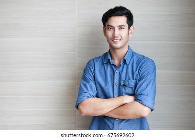 Young tall and handsome 30s Asian man crossing his arm over the chest and looking at camera with eyes contact in self-confidence  manner