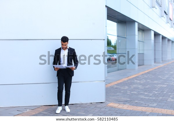 Young tall handsome arab entrepreneur guy student holds and studies, reads paper or documents, stands in full growth directly into camera near gray wall of business center. Bearded man dressed in