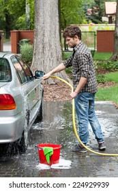 Young tall man spalshing his silver car by garden hose