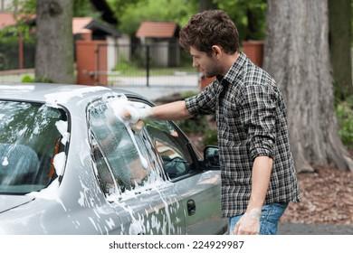 Young tall man washing his silver car