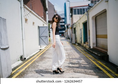 A young, tall, slim and elegant Indian Asian woman in a casual outfit walks down an alley in a street in Asia during the day. She is fashionably dressed and wearing sunglasses.