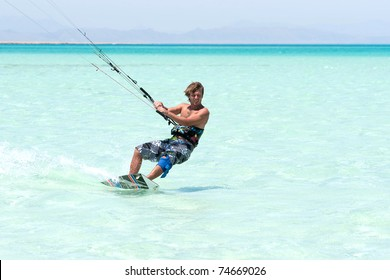 young tanned kiter with long hair  kiting in the surrounding of  turquoise sea spray