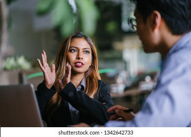 A young and tanned Southeast Asian business woman manager in a suit is coaching and mentoring a younger colleague in a trendy coworking office during the day. She is gesturing with her hands.