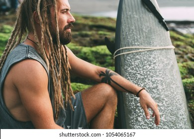 Young tanned surfer with long dreadlocks and beautiful tattoos sitting and watching the ocean on the mossy rocks in Indonesia, Bali, Canggu, Batu Bolong Beach.