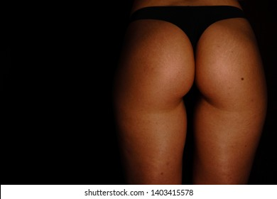 Young tanned woman with beautiful sporty buttocks and slim waistline - isolated on black wearing black shorts style underwear