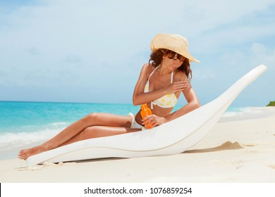 Young tanned woman in bikini sit at chaise-longue and apply sun-protection cream to her skin on the beach. Happy woman vacation. Relax on the beach.Protection of skin on the beach at summertime