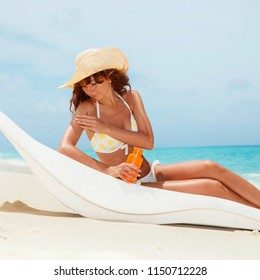 Young tanned woman in bikini sit at chaise-longue and apply sun-protection cream to her skin on the beach. Happy woman vacation. Relax on the beach. Protection of skin on the beach at summer time