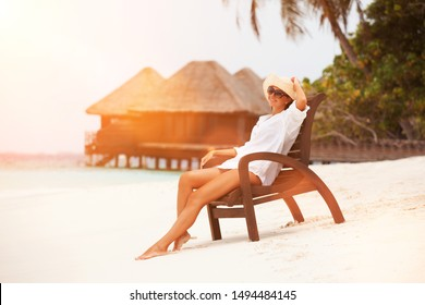 Young tanned woman sit at the chair and relax near bungalow of resort on the beach. Happy woman vacation, sunset background. Island lifestyle. Rest on the beach at summertime