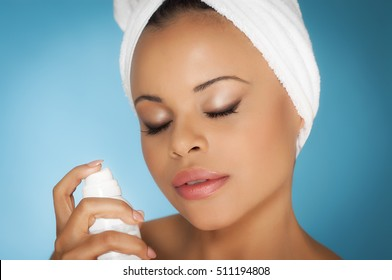 Young tanned woman in white bathroom towel grooming doing skincare ritual on blue background.
