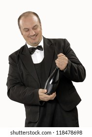 Young tasting man opening a red wine bottle.