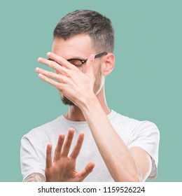 Young tattooed adult man covering eyes with hands and doing stop gesture with sad and fear expression. Embarrassed and negative concept.