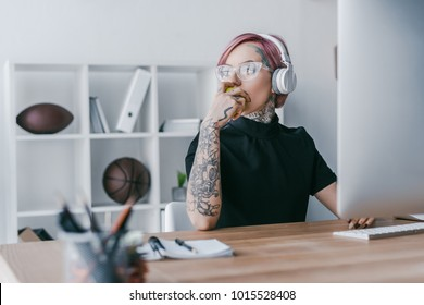 young tattooed businesswoman in headphones looking away at workplace