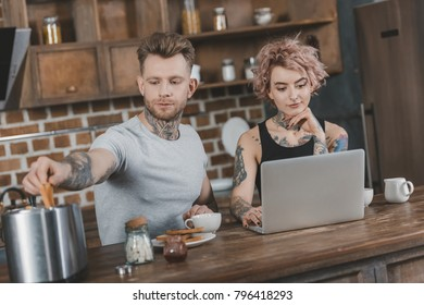 young tattooed couple using laptop during breakfast in kitchen