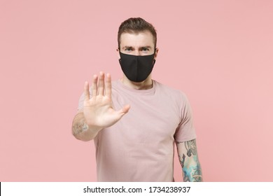Young tattooed man guy in pastel casual t-shirt, black face mask posing isolated on pink wall background studio portrait. People lifestyle concept. Mock up copy space. Showing stop gesture with palm