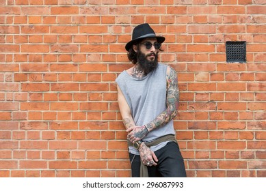 Young tattooed man portrait against brick wall in Shoreditch borough. London, UK. Hipster style