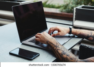 Young tattooed man working on laptop in a coffee shop. Rear view of hipster hands with tattoo busy using laptop at coworking office desk. Guy typing text on laptop with blank copy space screen mockup