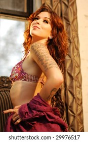 Young tattooed woman in lingerie with long reddish hair