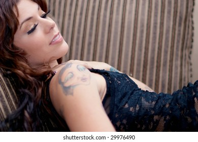 Young tattooed woman lying on old sofa