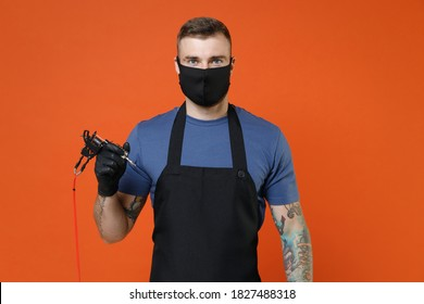 Young tattooer master artist man in blue t-shirt apron face mask hold in hand machine black ink jar equipment for making art body isolated on brown background studio. Tattoo translation life is fight.