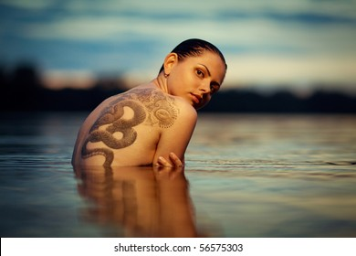 Young tattooing girl swiming in sea waves. An art photo. A beautiful landscape.