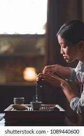 Young tea master pouring tea from teapot