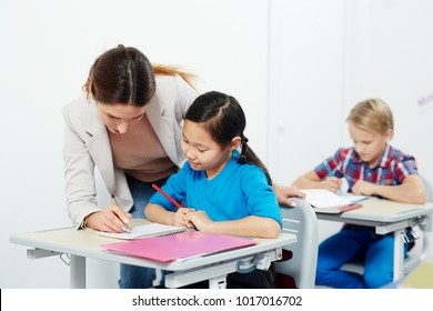 Young teacher checking notes of clever schoolgirl during individual work at lesson