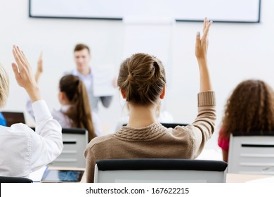 Young teacher in classroom standing in front of class