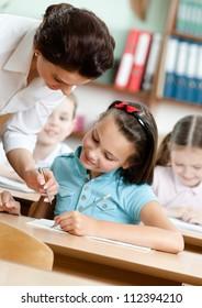 Junge Lehrer helfen den Schülern bei der Erfüllung ihrer Aufgabe