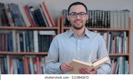 Young teacher holding book and looking at the camera