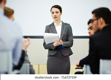 Young teacher listening to opinions and ideas of her students after lecture