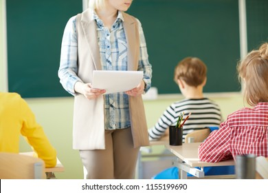 Young teacher moving among row of pupils desks and holding papers while giving task to elementary students at class