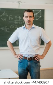 Young teacher near chalkboard in school classroom talking to class