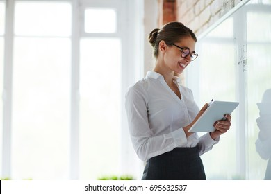 Young teacher with notepad standing by whiteboard in classroom