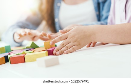 Young teacher and preschool girl playing together with colorful wood blocks, education and fun concept