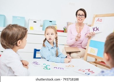 Young teacher showing cards with letters to children in kindergarten while learning alphabet