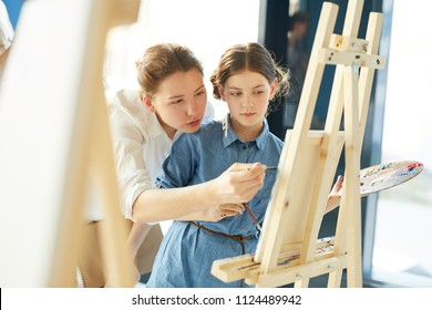 Young teacher showing one of pupils what should be corrected in her painting while pointing at easel