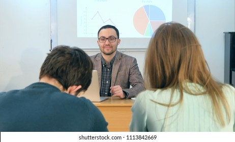 Young teacher sitting in school classroom with laptop, talking to students