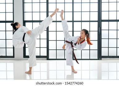 Young teacher of taekwondo and her student is acting of kick posture with white background and pattern.