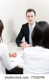 young teacher talking to asian women in the meeting room