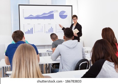 Young teacher teaching graphs drawn on whiteboard to college students in classroom