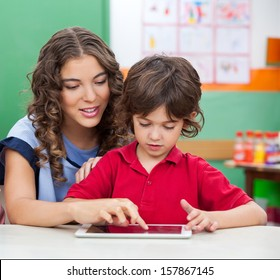 Young teacher teaching students to use digital tablet in classroom