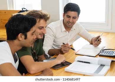Young teacher telling two students about corporate budgeting. Two young guys in casual tshirts listening to confident man in white shirt. Business school concept