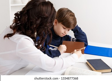 Young teacher trying to explain information to the boy. Educating together.