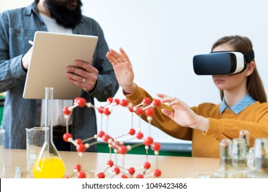 Young teacher using Virtual Reality Glasses and 3D presentation to teach students in chemistry class. Education, VR, Tutoring, New Technologies and Teaching Methods concept.