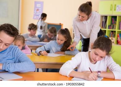 Young teacher woman and diligent schoolkids during lesson in classroom
