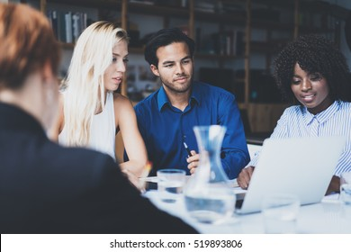 Young team of coworkers making great work discussion in modern office.Hispanic businessman talking with partners.Business people meeting concept.Horizontal, blurred background