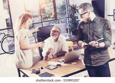 Young team of coworkers making great time brake during discussion in modern office.Bearded man laughing and girl holding cup of coffee.Business people meeting concept.Horizontal, blurred
