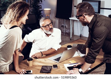 Young team of coworkers making great work discussion in modern coworking studio.Bearded man talking with colleagues about new startup project.Business people brainstorm concept.Horizontal, blurred